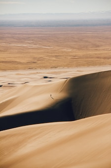 Verticaal schot van zandduinen en een droog gebied in de verte