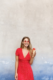 Verticaal schot van zomer meisje eten van ijs in de buurt van straatmuur en glimlachen naar de camera