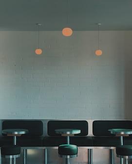 Verticaal schot van zwarte krukken naast sokkeltafels en banken binnen een koffiehuis