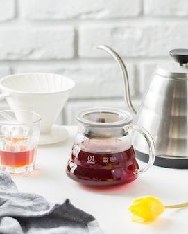 Verticaal selectief close-upschot van een glaswaterkruik voor thee dichtbij een kop en een ketel op een lijst