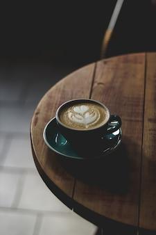Verticaal selectief close-upschot van koffie met lattekunst in een blauwe ceramische kop op een houten lijst