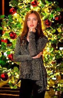 Verticaal shot van een mooi jong meisje voor een kerstboom