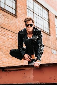 Verticaal shot van een stoere man met een zwart leren jas op het dak Gratis Foto