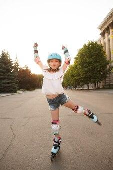 Verticaal shot van volledige lengte van een klein meisje met beschermende kleding, skaten in de stad in de zomer