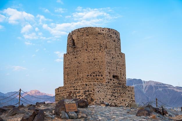 Verticaal van de historische al rabi-toren tegen de blauwe bewolkte hemel in de verenigde arabische emiraten