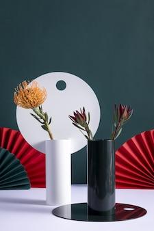 Verticaal van decoratieve vazen met protea en billbergia bloemen met chinese vouwwaaiers