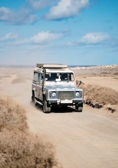 Verticaal van een off-road auto die zich in een woestijnweg beweegt