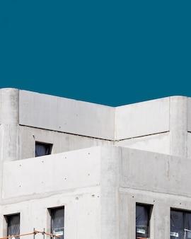 Verticaal van een wit concreet gebouw onder de blauwe hemel