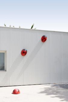 Verticaal van een witte muur met schattige lieveheersbeestje versieringen erop