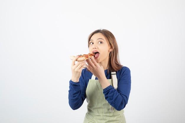 Verticaal, van, jonge vrouw, in, schort, etende, pizza, op, white