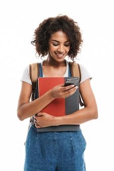 Verticaal, van, jonge vrouw, vervelend, rugzak, vasthouden, oefenboeken, en, gsm, geïsoleerde, op, witte muur
