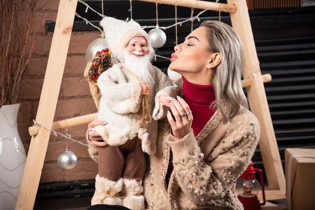 Verticaal, van, jonge vrouw, zitten op vloer, en, vasthouden, een, kerstman, speelbal., hoge kwaliteit, foto