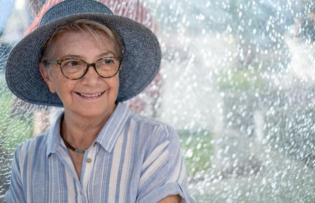 Verticaal, van, senior vrouw, vervelend, stro hoed, zittende, in, winkelcentrum, het glimlachen