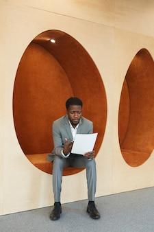 Verticaal volledig lengteportret van jonge afro-amerikaanse zakenman die documenten leest terwijl hij in eivormige oranje loungezone van modern bureau of coworkingruimte zit