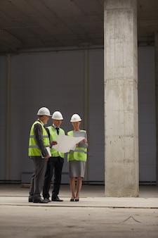Verticaal volledig lengteportret van zakenmensen die hardhats dragen en plannen houden terwijl zij op bouwplaats binnen staan,