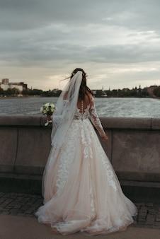 Verticaal volledig lichaam dat van een bruid is ontsproten die witte toga en huwelijkskleding draagt die zich op een brug bevindt