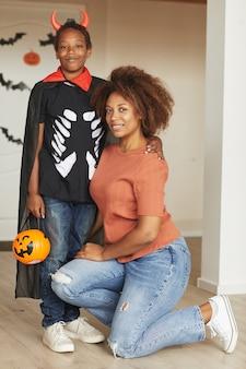 Verticaal volledig schot van mooie vrouw en haar preteen zoon die weinig duivelskostuum voor halloween draagt