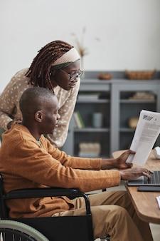 Verticaal zijaanzicht portret van afro-amerikaanse man met rolstoel die vanuit huis werkt met vrouw die over zijn schouder kijkt, kopieer ruimte