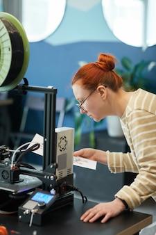 Verticaal zijaanzichtportret van jonge roodharige vrouw die 3d-printer in techniekklasse gebruikt