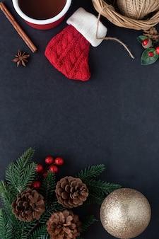 Verticaal zwart graniet met rode sok, dennenblad en kegels, hulstballen, bal en kop chocolade.