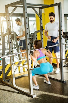 Verticale achteraanzicht van aantrekkelijk vorm jong meisje doet squats oefeningen met een balk achter de nek terwijl personal trainer naast haar in de zonnige sportschool staat.