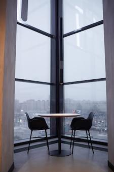 Verticale achtergrondafbeelding of tafelzitplaatsen door kamerhoge ramen met uitzicht op de stad, kopieer ruimte