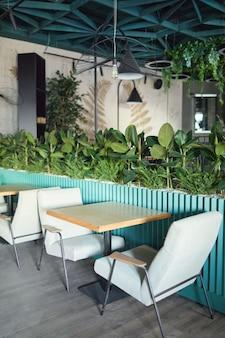 Verticale achtergrondafbeelding van eco-vriendelijk café-interieur met focus op gezellige zithoek met fauteuils en tafel versierd met verse groene planten, kopieer ruimte