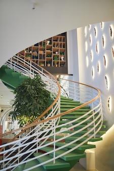Verticale achtergrondafbeelding van milieuvriendelijk architectonisch ontwerp met focus op wenteltrap versierd met groene planten, kopieer ruimte