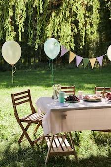 Verticale achtergrondafbeelding van zomer picknicktafel buiten versierd met ballonnen voor verjaardagsfeestje...