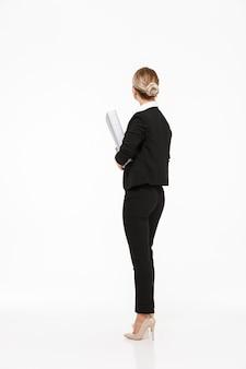 Verticale achtermening van blonde bedrijfsvrouw die grote omslag over witte muur houdt