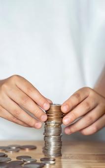 Verticale afbeelding kid hand stapelen sterling pond munt en penningen stuivers op houten tafel met kopie ruimte
