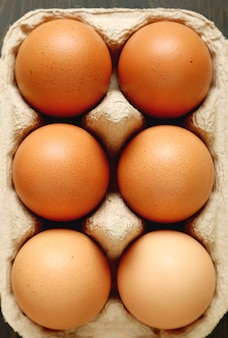 Verticale afbeelding van biologische kippeneieren in kartonnen doos