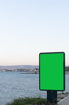 Verticale afbeelding van een groen scherm voor advertenties met uitzicht op de oceaan, een uitstekende ruimte voor uw tekst