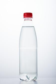 Verticale afbeelding van een plastic fles met rood deksel gevuld met water op witte achtergrond