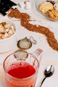 Verticale afbeelding van een rode theekop op de voorgrond op verweerde witte houten planken met suikerklontjes verspreid over de tafel en plaat met theegebak in de bovenhoek