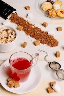 Verticale afbeelding van een rode theekop op verweerde witte houten planken met suikerklontjes verspreid over de tafel en plaat met theegebak in de bovenhoek