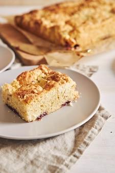 Verticale afbeelding van een stuk heerlijke jerry crumble sheet-cake op een witte houten tafel