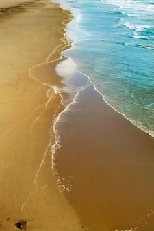 Verticale afbeelding van het strand omgeven door de zee onder het zonlicht
