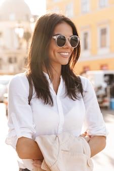 Verticale afbeelding van lachende brunette vrouw in shirt en zonnebril