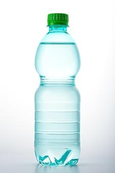 Verticale afbeelding van plastic schone fles met groene deksel gevuld met water op witte achtergrond