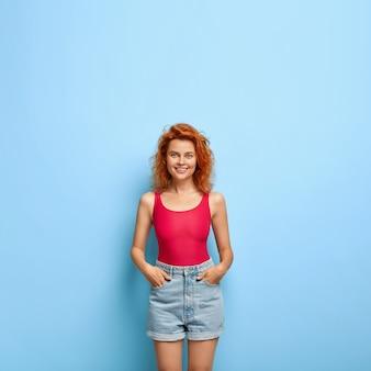 Verticale afbeelding van slanke gember jonge vrouw gekleed in rood vest en denim shorts, houdt handen in de zakken