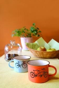 Verticale afbeelding van twee kopjes koffie met wazig fruit en planter op de achtergrond