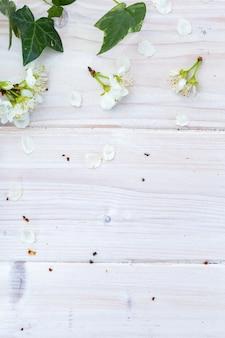 Verticale afbeelding van witte lentebloemen en bladeren op een houten tafel, plat leggen