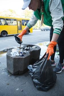 Verticale bijgesneden opname van een vrouwelijke activist die afval verzamelt in de straten van de stad