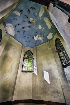 Verticale binnenopname van een gebouw met boogramen en een schilderij aan het plafond