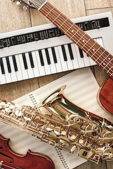 Verticale bovenaanzicht van verschillende muziekinstrumenten: synthesizer, gitaar, saxofoon en viool liggend op de bladen voor muzieknoten over houten vloer. muziekinstrumenten. muziekapparatuur