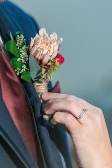 Verticale close-up die van een bruidegom is ontsproten die zijn boutonnière aan zijn kostuumjasje heeft vastgemaakt