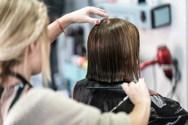 Verticale close-up die van een kapper is ontsproten die het korte haar van een vrouw in een schoonheidssalon snijdt