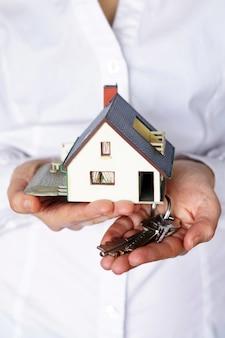 Verticale close-up die van een persoon is ontsproten die aan het kopen of verkopen van een huis denkt