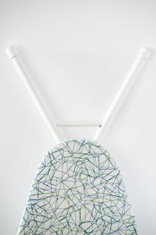 Verticale close-up die van een strijkplank is ontsproten die op een witte muur wordt geleund